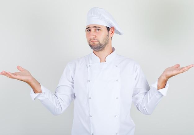Männlicher koch, der hilflose geste in der weißen uniform zeigt und verwirrt aussieht