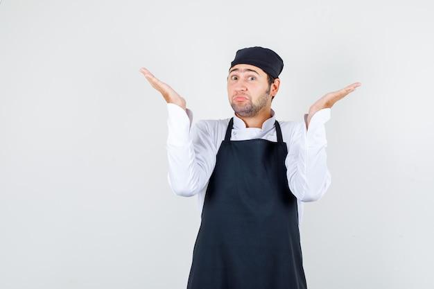 Männlicher koch, der hilflose geste in uniform, schürze und verwirrter vorderansicht zeigt.