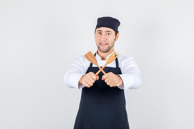 Männlicher koch, der hölzerne gabel und spatel in uniform, schürze hält und fröhlich schaut, vorderansicht.
