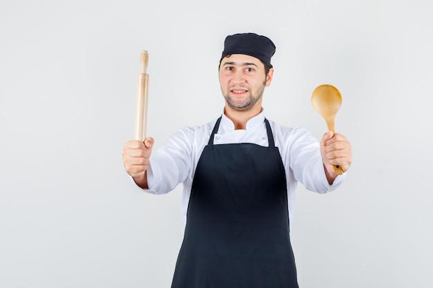 Männlicher koch, der hölzernen löffel und nudelholz in einheitlicher vorderansicht der schürze hält.