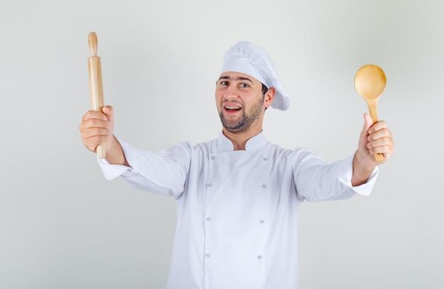 Männlicher koch, der holzlöffel und nudelholz in weißer uniform hält und fröhlich schaut