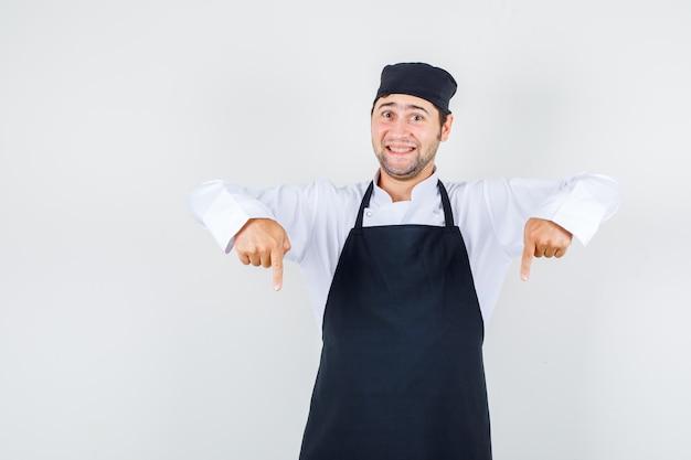 Männlicher koch, der in uniform, schürze unten zeigt und fröhlich, vorderansicht schaut.