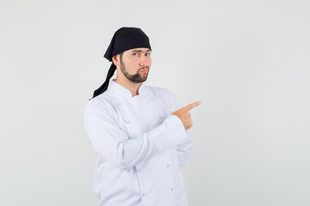 Männlicher koch, der in weißer uniform auf die seite zeigt und selbstbewusst aussieht. vorderansicht.