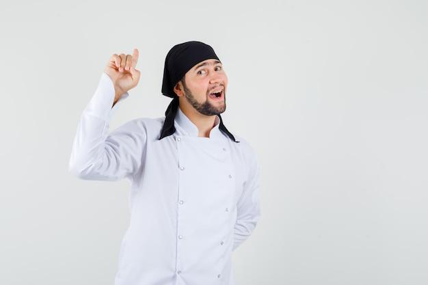 Männlicher koch, der in weißer uniform nach oben zeigt und fröhlich aussieht. vorderansicht.