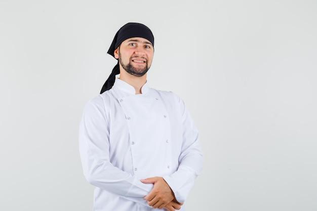 Männlicher koch, der in weißer uniform steht und fröhlich aussieht. vorderansicht.