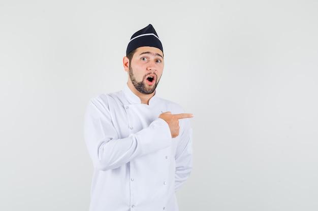 Männlicher koch, der in weißer uniform zur seite zeigt und neugierig aussieht, vorderansicht.