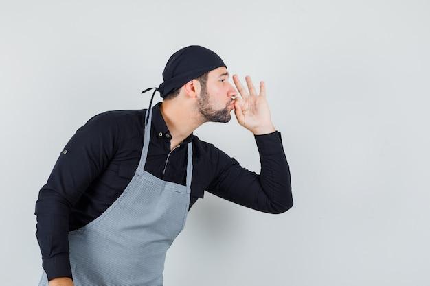 Männlicher koch, der köstliche geste im hemd zeigt, vorderansicht der schürze.