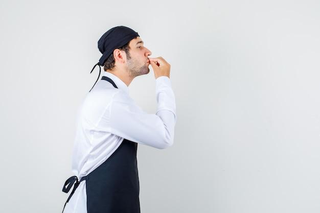 Männlicher koch, der köstliche geste in uniform, schürze macht.