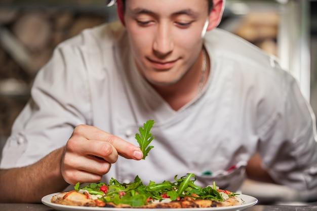 Männlicher koch, der köstliche vorspeise vorbereitet