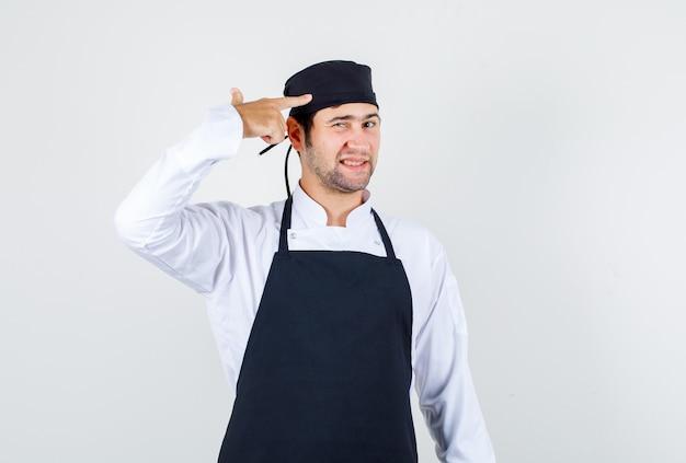 Männlicher koch, der kopf mit gewehrgeste in uniform, schürzenvorderansicht berührt.