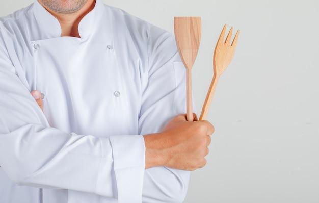 Männlicher koch, der küchenutensilien mit verschränkten armen in uniform hält