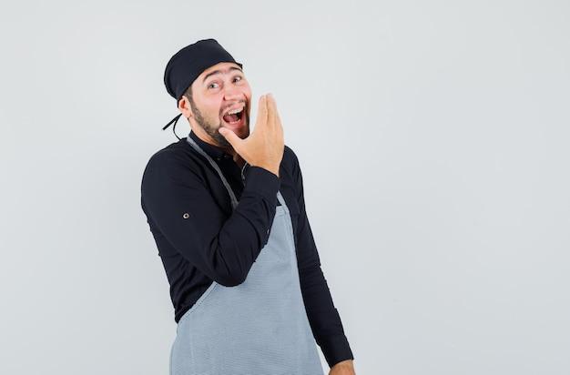 Männlicher koch, der laut in hemd, schürze lacht und glücklich schaut. vorderansicht.