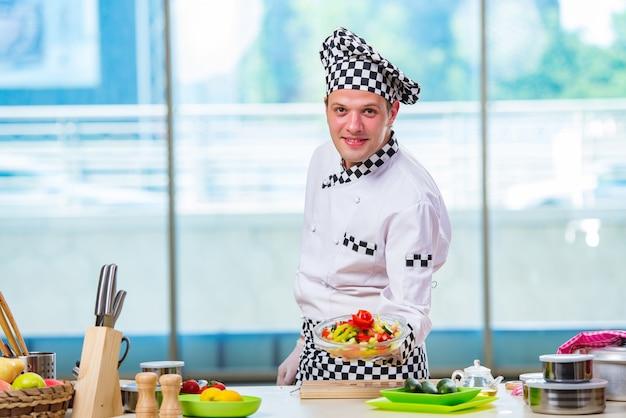 Männlicher koch, der lebensmittel in der küche zubereitet