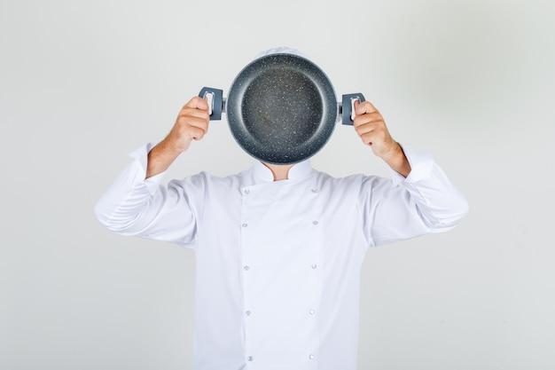 Männlicher koch, der leere pfanne über seinem gesicht in der weißen uniform hält
