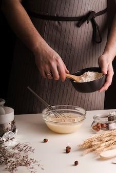 Männlicher koch, der mehl in schüssel der mischung hinzufügt