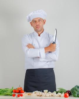 Männlicher koch, der messer mit verschränkten armen in der küche in uniform, hut und schürze hält