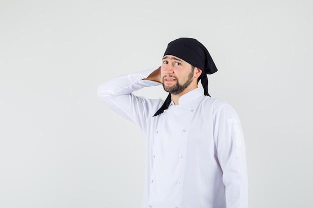 Männlicher koch, der mit der hand hinter dem kopf in weißer uniform steht und unentschlossen aussieht, vorderansicht.