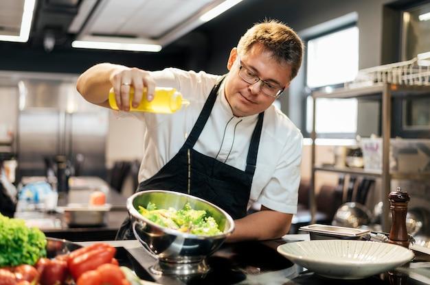 Männlicher koch, der öl im salat hinzufügt