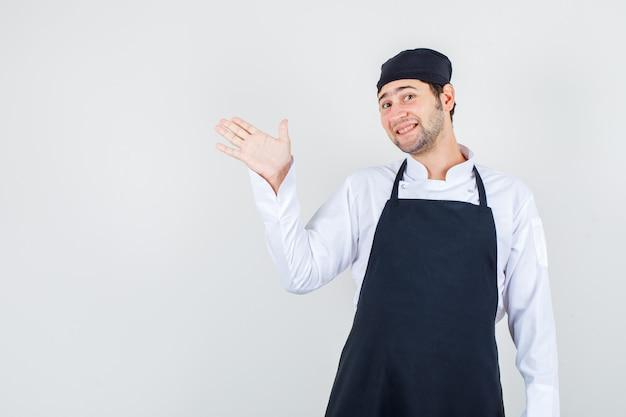 Männlicher koch, der palme zeigt, um besucher in uniform, schürze und fröhlich aussehend zu leiten. vorderansicht.