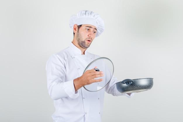 Männlicher koch, der pfanne und glasdeckel in der weißen uniform hält und überrascht schaut.