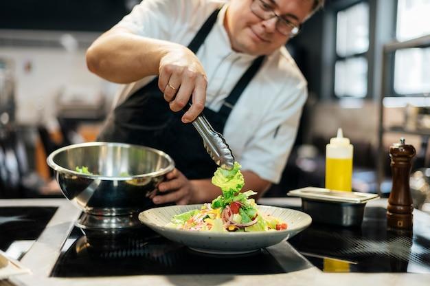 Männlicher koch, der salat auf teller setzt