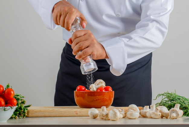 Männlicher koch, der salz in essen in der küche in uniform und schürze hinzufügt