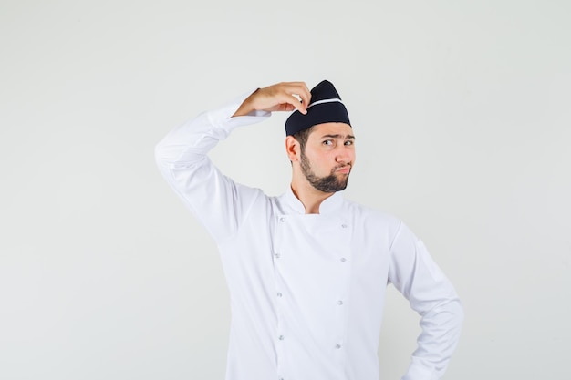 Männlicher koch, der seinen kopf in weißer uniform berührt und nachdenklich aussieht, vorderansicht.
