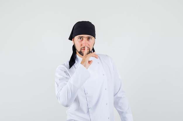 Männlicher koch, der stillegeste in weißer uniform zeigt und vorsichtig aussieht. vorderansicht.