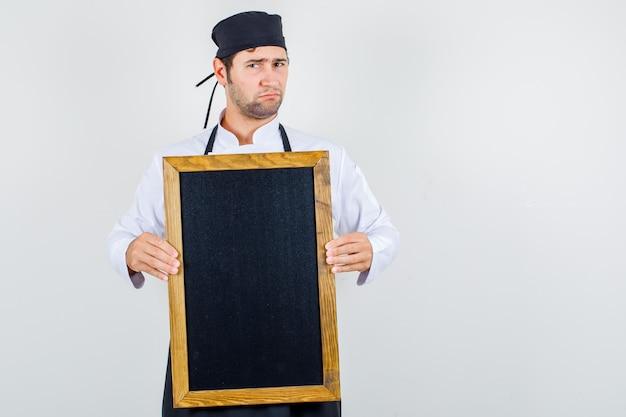 Männlicher koch, der tafel in uniform, schürze hält und unzufrieden aussieht. vorderansicht.