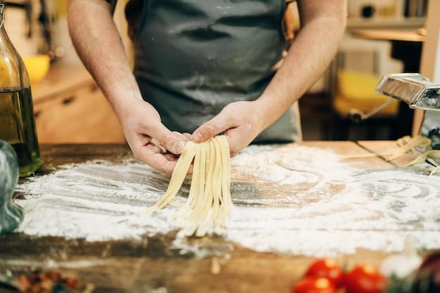 Männlicher koch, der teig kocht und nudelmaschine vorbereitet