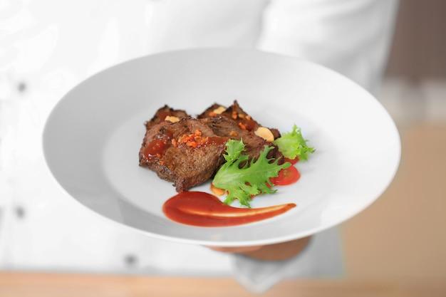 Männlicher koch, der teller mit fleisch, nahaufnahme hält