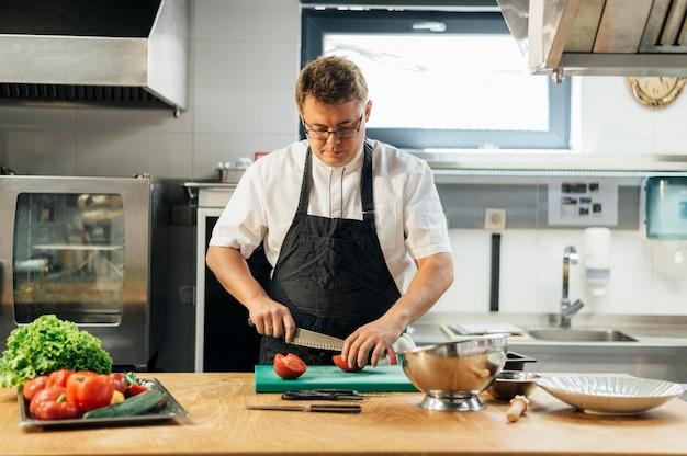 Männlicher koch, der tomaten in der küche schneidet