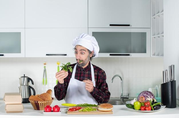 Männlicher koch der vorderansicht, der grüns in der küche hält