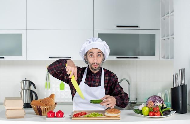 Männlicher koch der vorderansicht, der gurke und messer in der küche hält