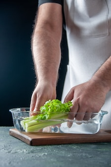 Männlicher koch der vorderansicht, der sellerie vom teller mit wasser auf dunklem wandsalat-diätmahlzeit-farbfoto-nahrungsmittelgesundheit herausnimmt