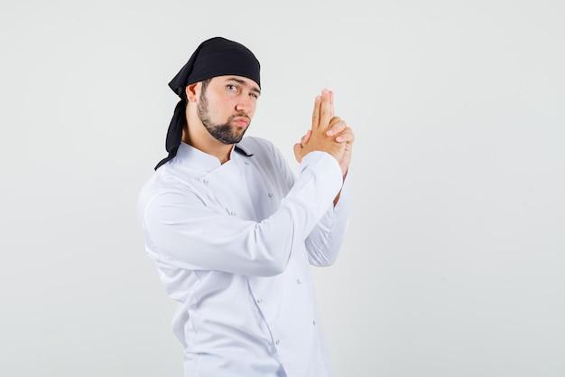 Männlicher koch, der waffengeste in weißer uniform zeigt und selbstbewusst aussieht, vorderansicht.