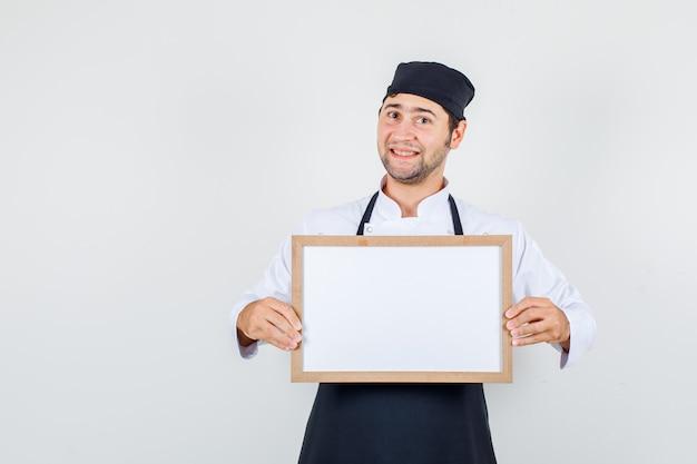 Männlicher koch, der weiße tafel in uniform, schürze hält und fröhlich schaut. vorderansicht.