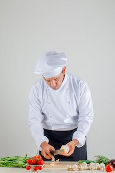 Männlicher koch, der zwiebel auf holzbrett in uniform, schürze und hut in der küche schält