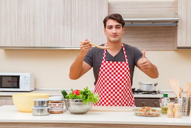 Männlicher koch des mannes, der lebensmittel in der küche zubereitet