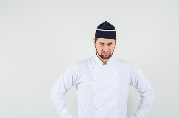 Männlicher koch freut sich in weißer uniform und sieht nervös aus, vorderansicht.