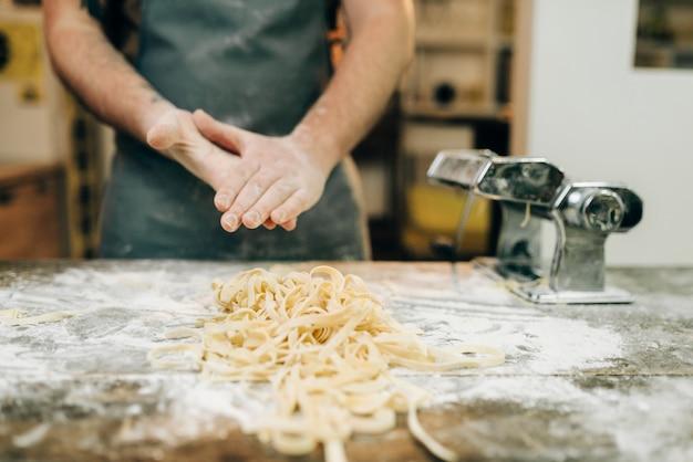 Männlicher koch gegen hölzernen küchentisch mit ungekochter hausgemachter fettuccine und nudelmaschine. traditionelle italienische küche. vorbereitungsprozess