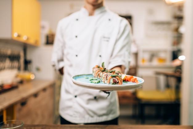 Männlicher koch halten sushi-rollen auf teller, japanischer küchenvorbereitungsprozess.