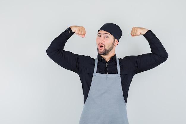 Männlicher koch im hemd, schürze, die muskeln zeigt und kraftvoll, vorderansicht schaut.