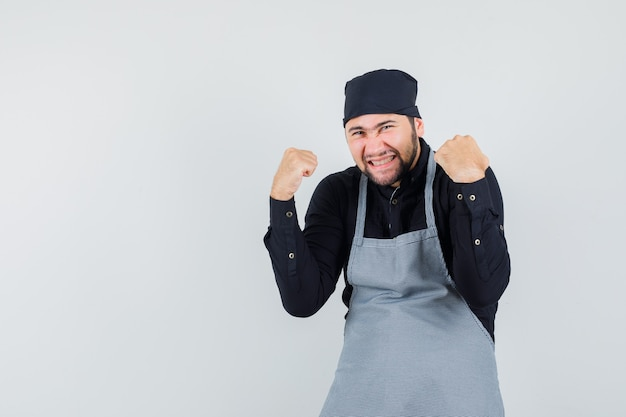 Männlicher koch im hemd, schürze, die siegergeste zeigt und glückliche vorderansicht schaut.