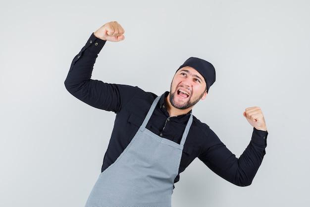 Männlicher koch im hemd, schürze, die siegergeste zeigt und glückselige vorderansicht schaut.