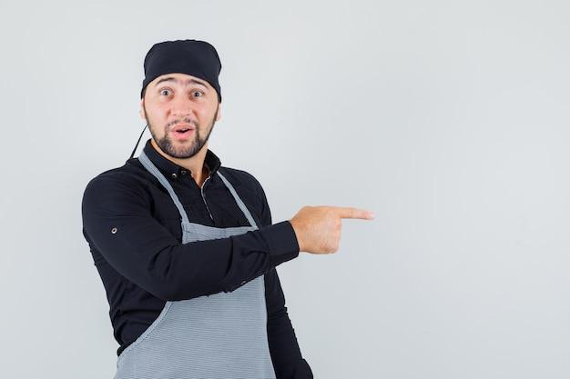 Männlicher koch im hemd, schürze zeigt zur seite und schaut erstaunt, vorderansicht.