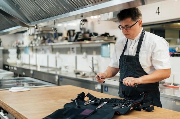 Männlicher koch in der küche, die seine werkzeuge vorbereitet