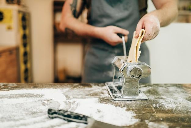 Männlicher koch in der schürze arbeitet mit nudelmaschine auf hölzernem küchentisch. selbst gemachter spaghetti-kochprozess