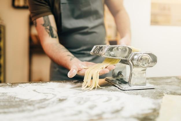 Männlicher koch in der schürze, die frische hausgemachte fettuccine in der nudelmaschine auf hölzernem küchentisch kocht