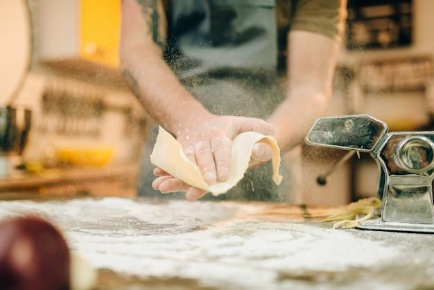 Männlicher koch in der schürze, die teig kocht und nudelmaschine auf hölzernem küchentisch vorbereitet